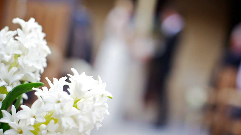 Photography of a wedding floral arrangement with the bride and groom in the background