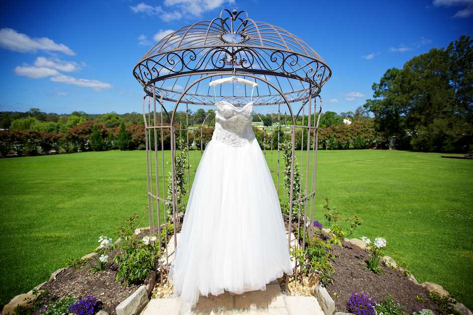 Landscape photograph of wedding dress hanging in gazebo